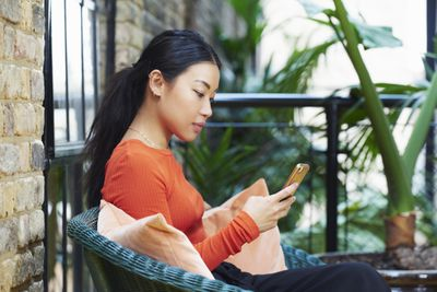 A woman is sitting on her porch and looking at her cell phone.