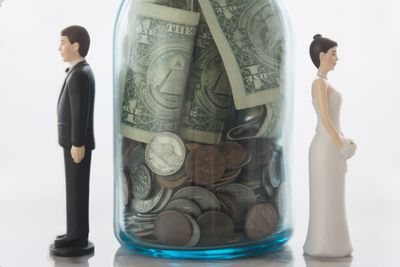 bride and groom wedding cake toppers stand on either side of a jar filled with money indicating spliting assets during a divorce