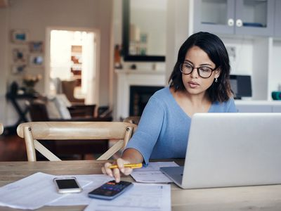 A woman at her kitchen table with a calculator and laptop, calculating her credit card payments and costs