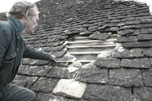 Man measuring a large hole on a roof and realizing why insuring a home for replacement costs is important