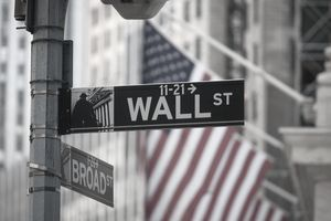 A sign for Wall Street and American flags in New York, U.S.