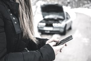 Woman Stands With Cellphone on Road in Front of Broken-Down Car With Hood Up