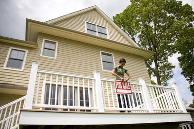 Woman hanging For Sale sign on porch