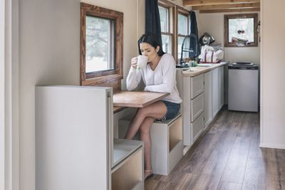 Woman sits at a small table drinking coffee in a tiny home.