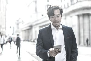 businessman walking in the street, using his phone