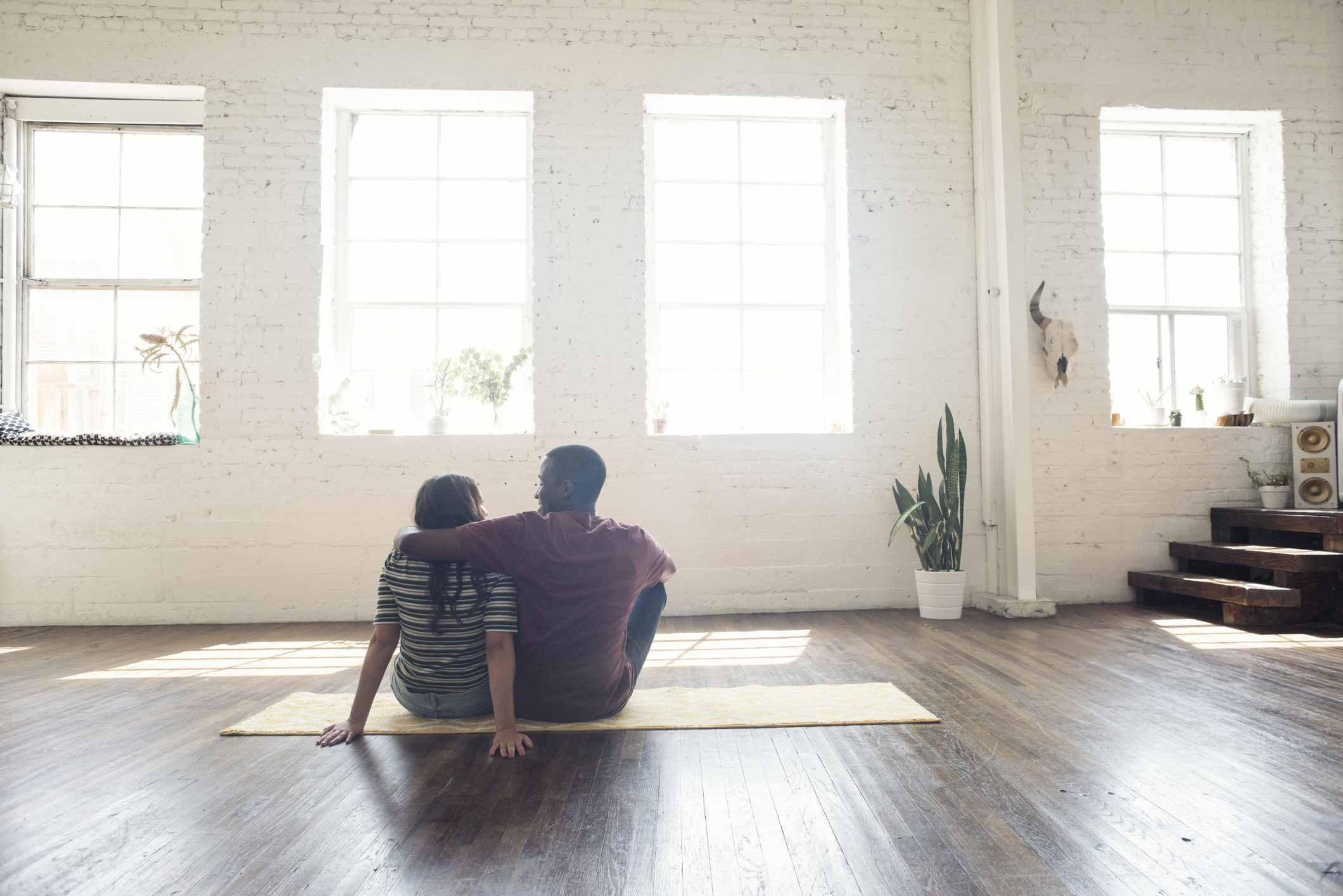 A couple sitting on the floor of their new, less-expensive residence