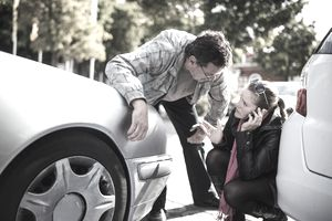 Man and woman talking to each other between their cars after an accident.