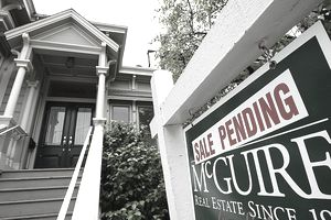"A real estate sign with a ""sales pending"" sticker in front of a house"