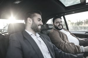 Two people in business attire sit in the front seats of a car