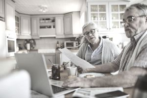 An older couple going over documents and using a laptop in their kitchen