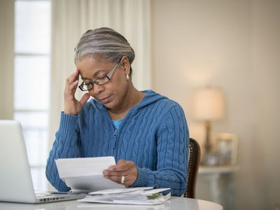 Woman in a blue cable-knit sweater reviews paperwork at her home laptop.