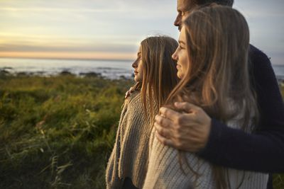 A father and his daughters look at the ocean