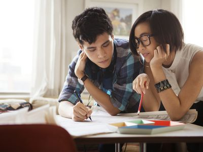 A young couple reviews documents at a table