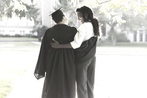 Mother and daughter in graduation gown hugging on campus
