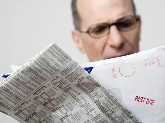 a man reads past due bill notice