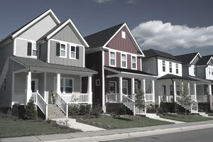 Street view shows a row of nearly identical houses, each with porches and stairs landing on the walk in front.