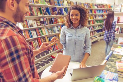 A young woman in a college bookstore hands over a credit card to pay for school supplies