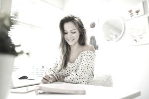 A woman sits at her desk and writes down a list of her goals.