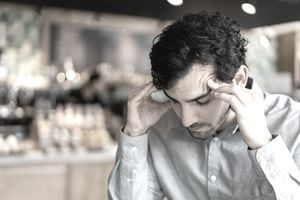 A man in a cafe presses his fingers to his temples in frustration and concern.