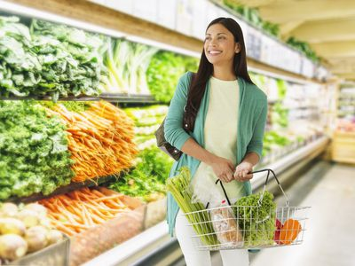 A smiling woman holding a shopping basket in the produce section of a grocery store where prices are low due to NAFTA agreements