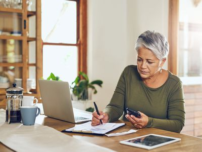 Middle-aged woman working on taxes with laptop, pad pf paper, and calculator.