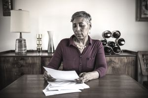 Woman (60yrs) paying bills at home