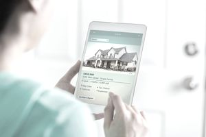 Woman using tablet to look at houses for sale online