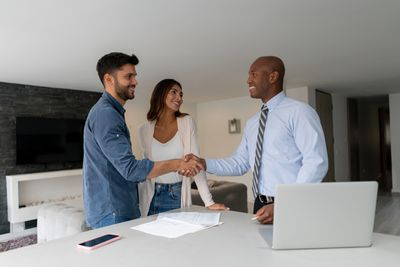 Couple buying a house and closing the deal with the real estate agent