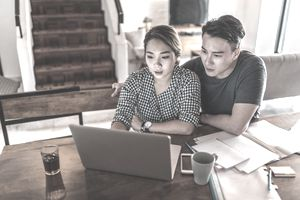A young couple sitting at their dining table using a laptop to make a debt reduction plan.