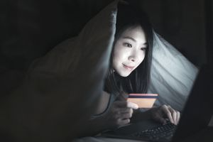 Close-up shot of young Asian woman shopping online with credit card and laptop, covering with duvet, lying on the bed in a dark environment.