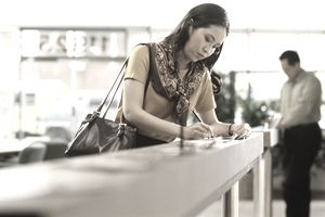 Woman in a bank filling out paperwork to get a covered bond