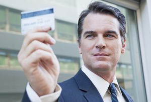 a man holding up a credit card