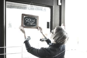 """Woman hanging """"Open"""" sign in her shop window"""