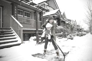Mother with son shoveling snow in winter