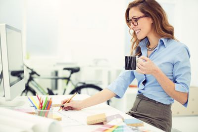 A smiling woman at a white home desk with a monitor, holding a cup of coffee
