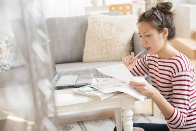 A woman works out how to consolidate her debt at her coffee table.