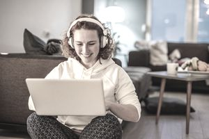 Woman sitting with laptop in lap wearing headphones