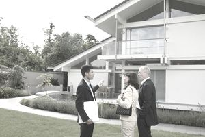 Businessman talking to couple, outside house, mid section