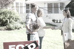 "Realtor congratulating family outside a house with a ""sold"" sign"