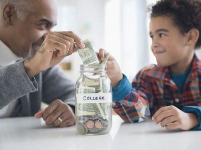 A grandparent and grandson add cash to a jar labeled