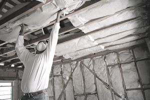 Construction worker installing insulation between ceiling struts