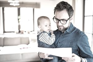 Man working in home office, holding his infant and looking at paperwork
