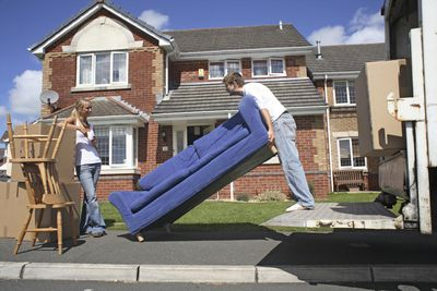 Young man lifting sofa standing on truck platform, woman watching standing by