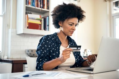 Woman holding credit card and reviewing her account online
