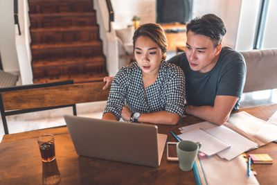 Serious couple using laptop while sitting at home