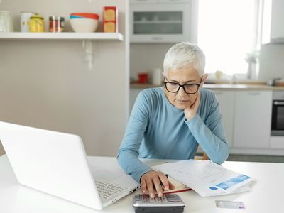 Woman in blue top with short gray hair working with a calculator and laptop in her kitchen.