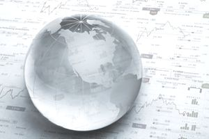 A glass globe on top of a page showing stock charts.