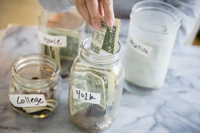 Hand putting money in to jars marked