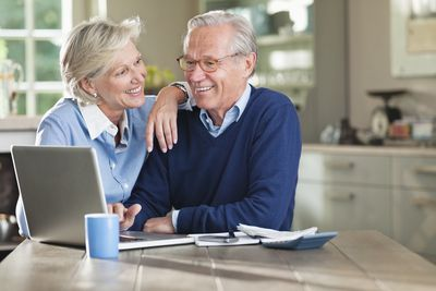 A retired couple using a laptop computer.