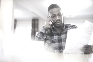 Man in blue flannel shirt on the phone at a table holding lots of paperwork.